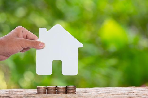 Wereld habitat dag, close-up foto van een stapel munten en hand met een model huis Gratis Foto