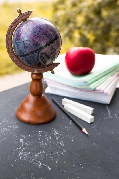 Wereldbol met notebooks en apple op het bord. Premium Foto