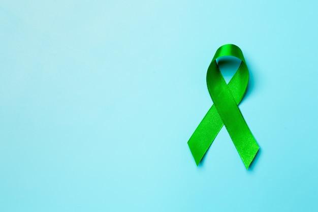 Werelddag voor geestelijke gezondheid. groen lint op blauwe achtergrond Gratis Foto