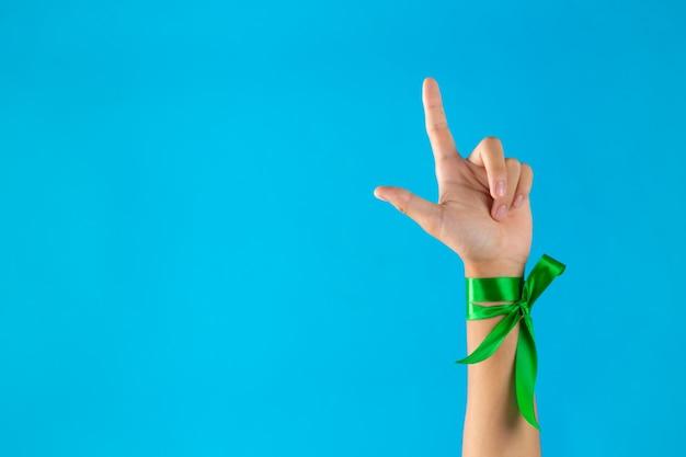 Werelddag voor geestelijke gezondheid. groene linten gebonden aan de pols op blauwe achtergrond Gratis Foto