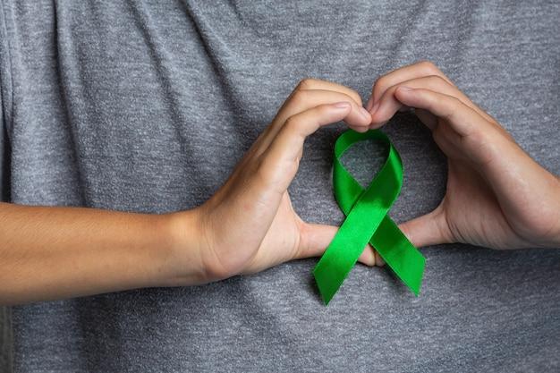 Werelddag voor geestelijke gezondheid. man's hand weergegeven: hartvormig rond een groen lint Gratis Foto