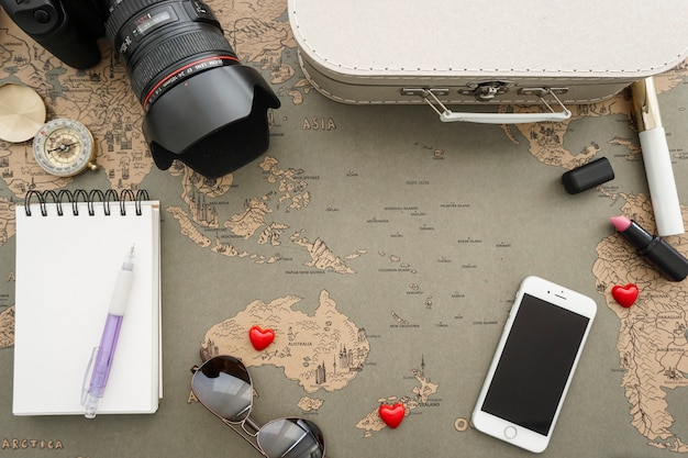 Wereldkaart achtergrond met een verzameling van reisartikelen Gratis Foto