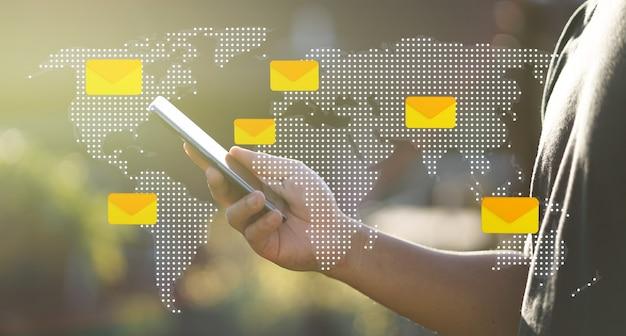 Wereldkaart bericht pictogrammen man hand met behulp van smartphone Premium Foto