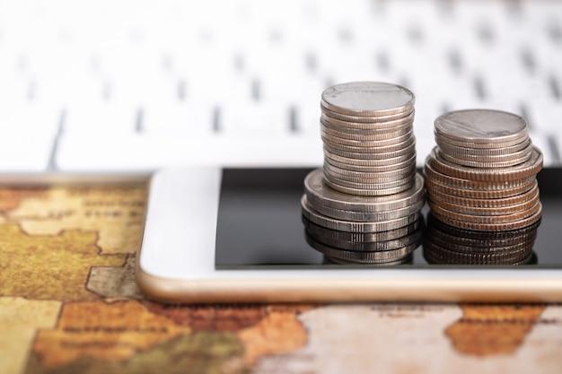 Wereldwijde business, geld, financiën en technologie concept. sluit omhoog van stapel muntstukken op slimme mobiele telefoon en wereldkaart met computertoetsenbord. Premium Foto