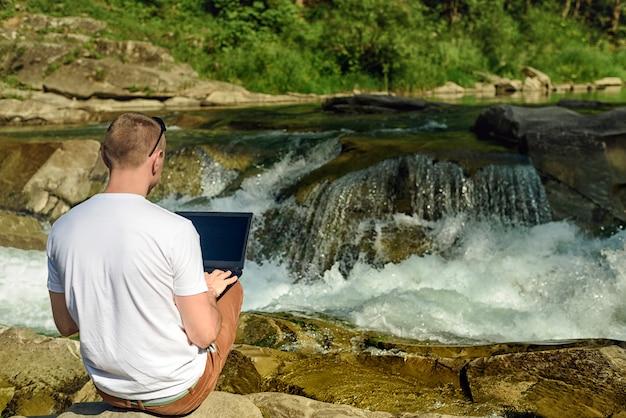 Werk in de natuur concept. mens met notitieboekjezitting bij de bank van rivier over de waterval en de groene bomen. achteraanzicht Premium Foto