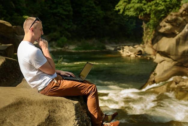 Werk in de natuur concept. nadenkend man met laptop zittend aan de oever van de rivier over de waterval. zijaanzicht Premium Foto