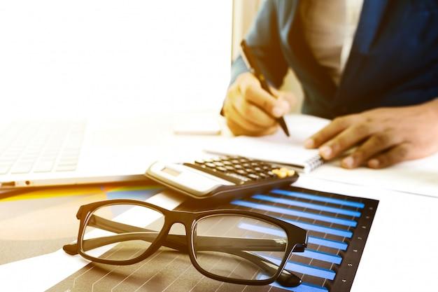 Werken op desktop laptopcomputer met calculator voor het maken van zaken Premium Foto