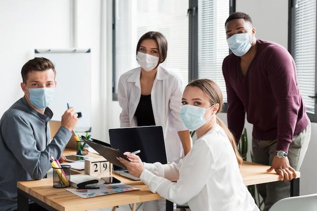 Werkend team op kantoor tijdens pandemie met gezichtsmaskers Gratis Foto