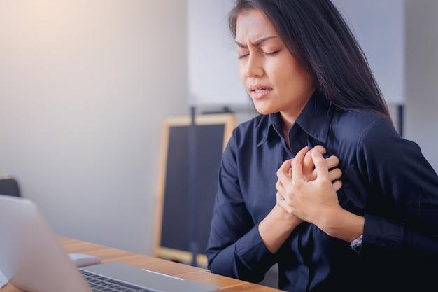 Werkend vrouwengezicht die en borst wegens hartinfarct lijden houden in bureau Premium Foto