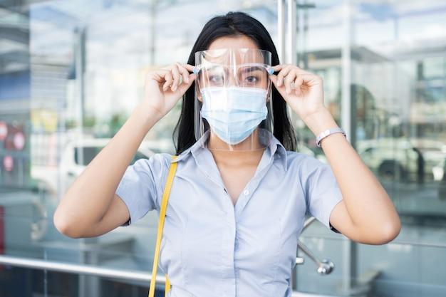 Werkende aziatische vrouw, hij draagt een masker en een gelaatsscherm ter bescherming tegen virussen. Premium Foto