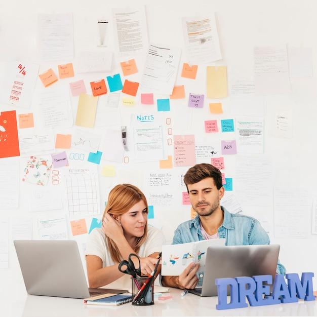 Werkende collega's die document op werkplaats met laptopskantoorbehoeften en naambord bekijken Gratis Foto