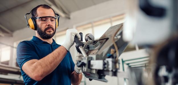 Werkende de zaagsnijmachine van de fabrieksarbeider werkende Premium Foto