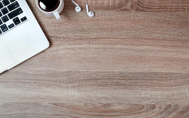 Werkende houten tafel met laptopcomputer en koffiekopje Premium Foto