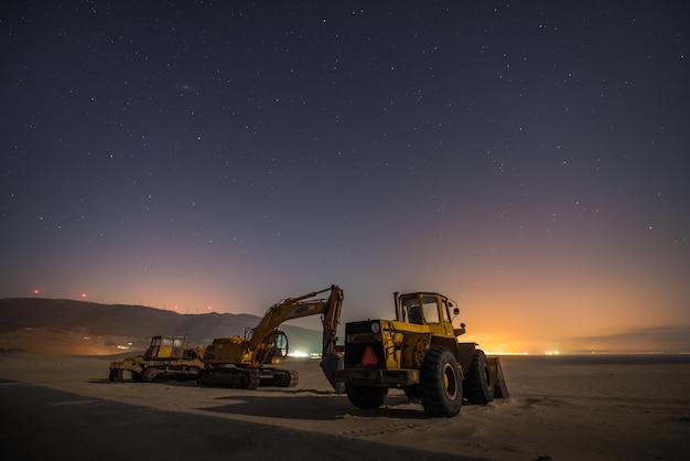 Werkende machines op een zandduin van het zuiden van spanje in de nacht Premium Foto