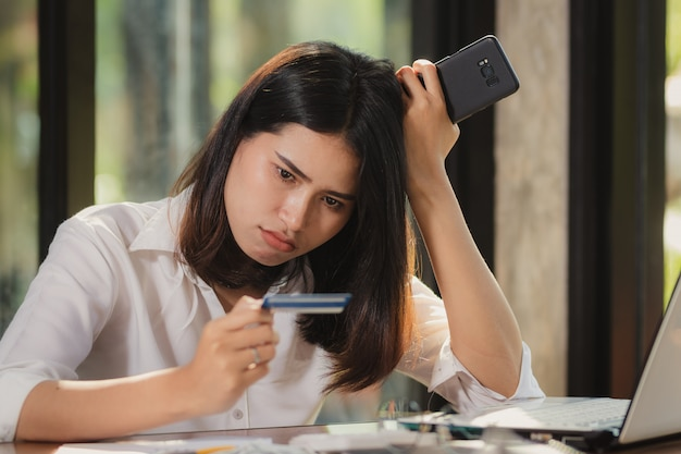 Werkende vrouw met behulp van smartphone en kijken naar een kaart met verwondering. Premium Foto