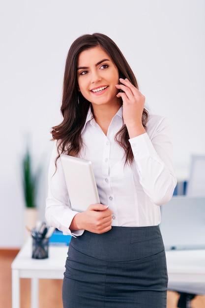 Werkende zakenvrouw bellen op kantoor Gratis Foto