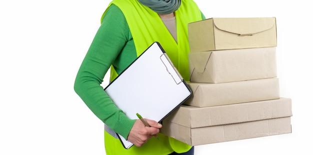 Werkneemster in een groen vest dat zich dichtbij heel wat document dozen met lege orde bevindt, leveringsconcept. Premium Foto