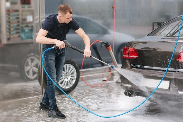 Werknemer auto reinigen met water onder hoge druk. Premium Foto
