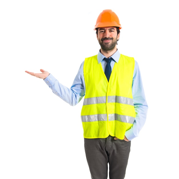 Werknemer die iets op witte achtergrond houdt Gratis Foto