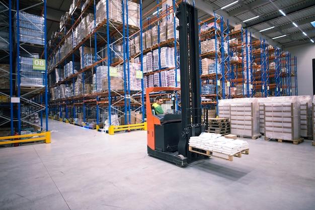 Werknemer heftruckmachine bedienen en goederen verplaatsen in groot magazijncentrum Gratis Foto