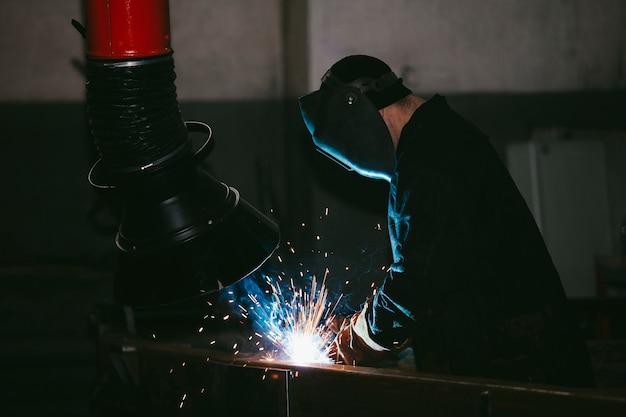 Werknemer in de fabriek in de helm is van ijzer in het lasproces heldere vonken Premium Foto