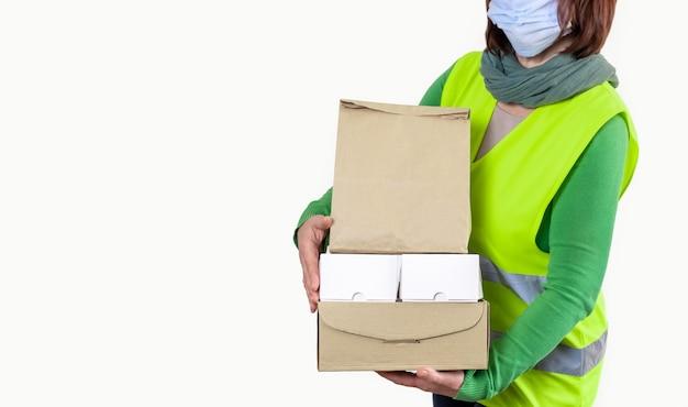 Werknemer in een groen vest met veel kartonnen dozen, leveringsconcept. Premium Foto