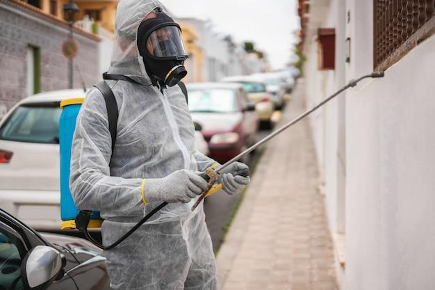 Werknemer in hazmat pak dragen gasmasker bescherming tijdens het desinfecteren in de straat van de stad Premium Foto
