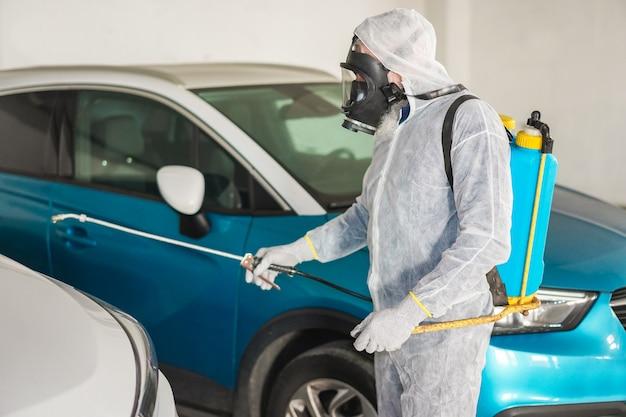Werknemer in hazmat pak met gasmasker bescherming tijdens het desinfecteren in de straat Premium Foto