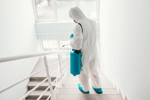 Werknemer in steriel uniform, met handschoenen en gezichtsmasker steriliserende reling op school. Premium Foto