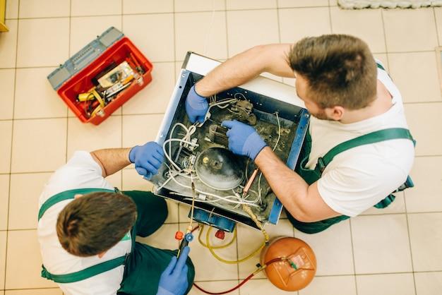 Werknemer in uniform probleem met koelkast thuis tot vaststelling van. reparatie van koelkastbezetting, professionele service Premium Foto