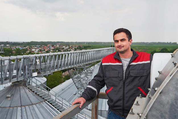 Werknemer in uniform tegen de agri-gebouwen op de achtergrond Gratis Foto