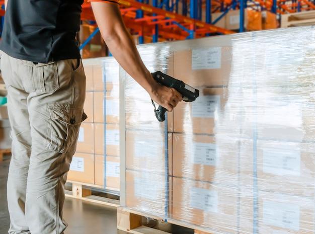 Werknemer man hand met streepjescodescanner met scannen op lading pallet in magazijn Premium Foto