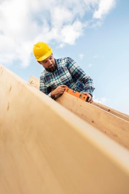 Werknemer met bouwvakker en niveau die het dakhout van het huis controleert Gratis Foto