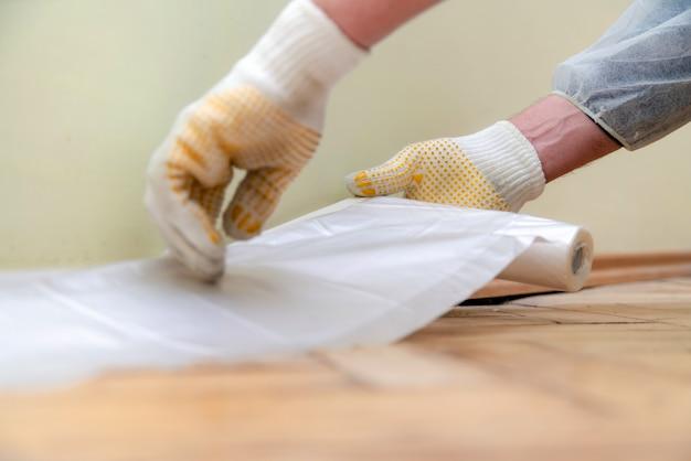 Werknemer met handschoenen en beschermende werkkleding cellofaan plakken. Premium Foto