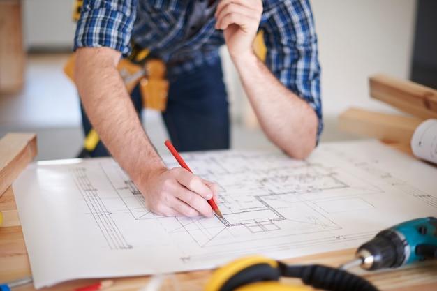 Werknemer met wijzigingen op blauwdruk van huis Gratis Foto