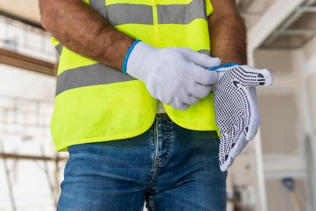 Werknemer op een bouwplaats die handschoenen zet Gratis Foto