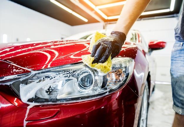 Werknemer rode auto met spons op een wasstraat wassen. Premium Foto