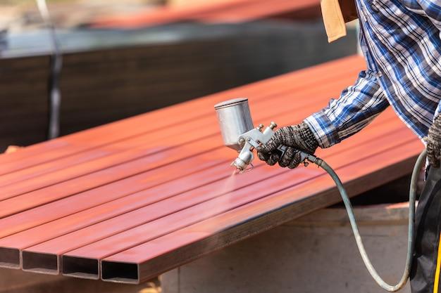 Werknemer spuit verf op stalen buis om roest op het oppervlak te voorkomen Premium Foto