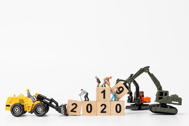 Werknemer team minatures maken houten blok met nummer 2020 Premium Foto