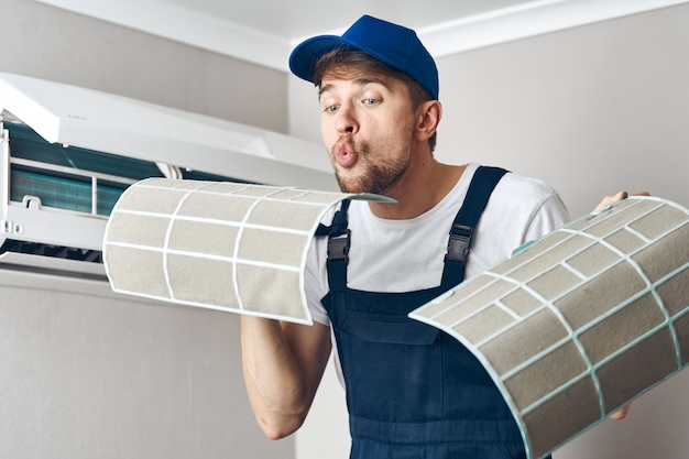 Werknemer voert reparatiewerkzaamheden en airconditioning uit Premium Foto