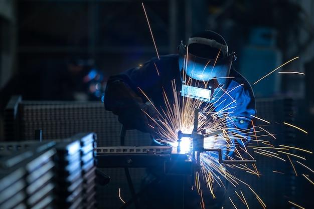Werknemers dragen industriële uniformen en gelast ijzeren masker bij stalen lasinstallaties. Premium Foto