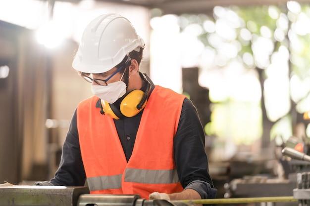 Werknemers fabriek man met gezichtsmasker en werken bij zware machine. Premium Foto