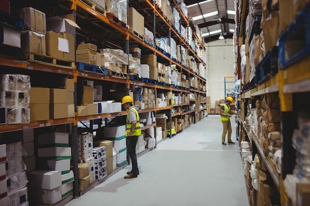 Werknemers in magazijn dragen helmen Premium Foto