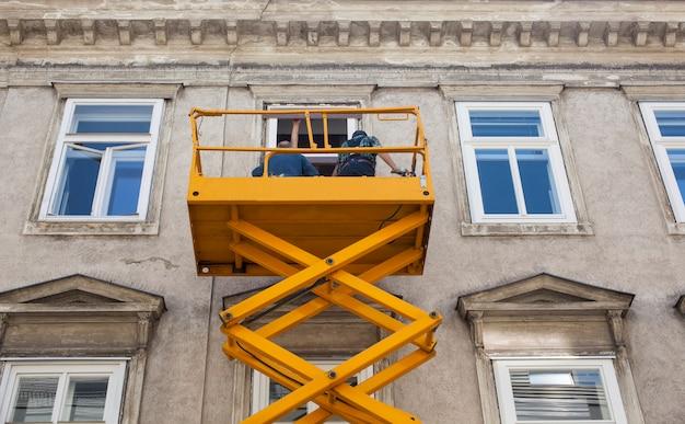 Werknemers op een hoogwerker renoveren de gevel van een gebouw Premium Foto