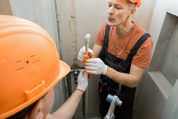 Werknemers solderen muurbuizen voor een ingebouwde douche Premium Foto