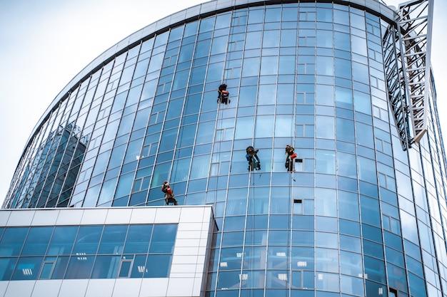 Werknemers wassen van ramen in het kantoorgebouw Gratis Foto