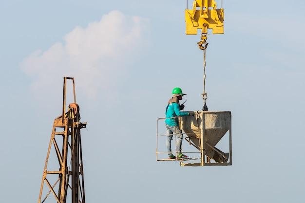 Werknemers werken op de kraan in de bouwplaats Gratis Foto
