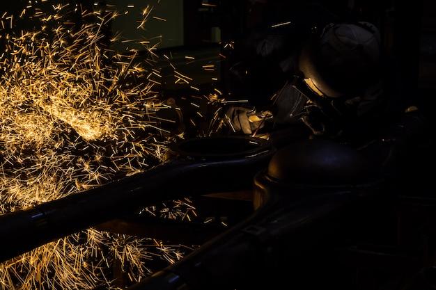 Werknemers zijn groeven met koolstof lasdraden met vonken Premium Foto