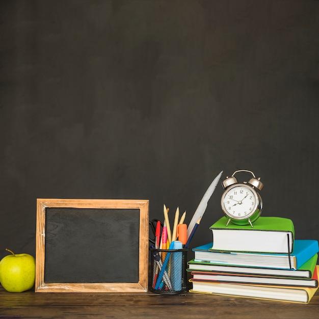 Werkplaats met schoolbordboeken en kantoorbehoeften Gratis Foto