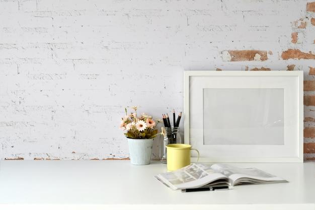 Werkplek en kopie ruimte, stijlvolle werkruimte met mockup lege poster, vintage boeken en kamerplant. Premium Foto